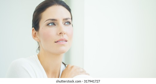 Beautiful natural European woman sitting in daylight at window with serene expression. Blue eyes and dark hair.