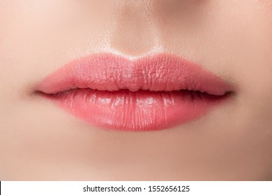 Beautiful natural female lips close-up with pink permanent makeup stick.