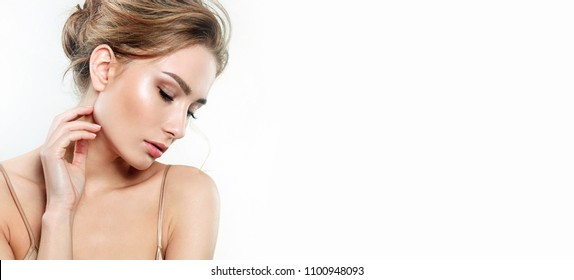 A beautiful natural girl with smooth skin and natural make-up on a white background. The hairs are gathered in a bun at the back of the head.