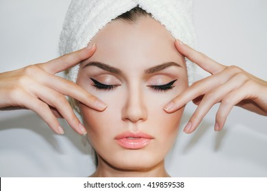 Beautiful natural girl woman after cosmetic procedures , facelift , facial massage , visit a beautician , massage lines. Beautiful woman with a towel on his head. Beautiful female.  Cosmetology