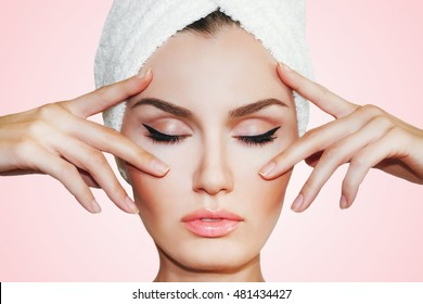 Beautiful natural girl woman after cosmetic procedures ,face-lift , facial massage , visit a beautician , massage lines. Beautiful woman with a towel on his head.
