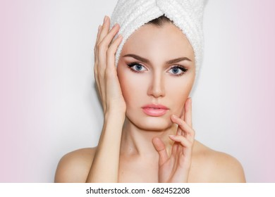 Beautiful natural girl woman after cosmetic procedures , face-lift , facial massage , visit a beautician , massage lines. Beautiful woman with a towel on his head.  Spa treatments