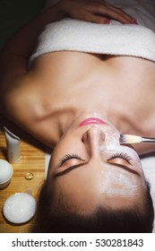 Beautiful natural girl woman in the spa salon, It makes a face massage, facial rejuvenation procedure, spa treatments. Visit a beautician, massage lines. Cosmetology.
