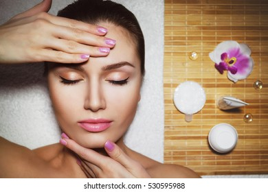 Beautiful natural girl woman in the spa salon, It makes a face massage, facial rejuvenation procedure, spa treatments. Visit a beautician, massage lines. Cosmetology. Massage Toffa