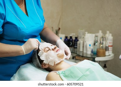 Beautiful natural girl woman in the spa salon, It makes a face mask, facial rejuvenation procedure, spa treatments. Visit a beautician, massage lines. Cosmetology.