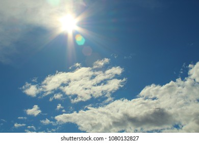 Beautiful natural glow of the sun. Beautiful blue sky and white fluffy clouds. Background. Landscape. Panorama.