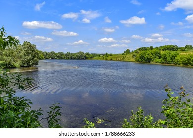 Beautiful natural landscape of a rural pond with lush green nature in a hilly area. Spring-summer panorama of the Uhroidy/Ugroedy village (Sumy region, Ukraine). Lake in the forest