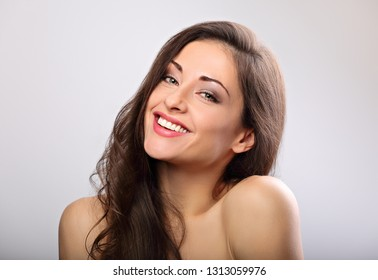 Beautiful natural makeup toothy smiling woman with long hair style. Skincare concept. Closeup portrait on blue background with empty copy space.