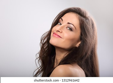 Beautiful natural makeup woman smiling with long hair style. Skincare concept. Closeup portrait on blue background with empty copy space