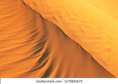 Beautiful natural pattern of golden desert sand ripples shaped by the wind