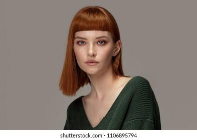 Beautiful natural redhead woman posing in fashionable sweater, looking at camera.