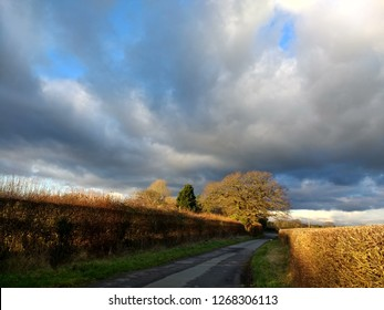 Beautiful natural rural landscape view in Warwickshire countryside near Shakespeare's birthplace with dramatic blue skies and rolling cloud over country lane and fields in Winter early evening light
