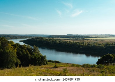 Beautiful natural scenery of river and green fields amidst trees during sunny summer day