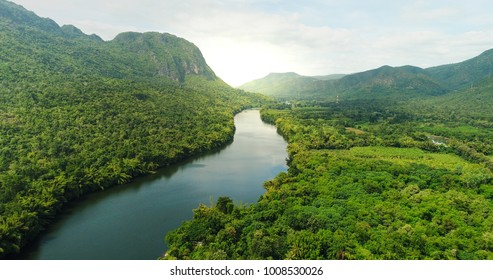 Beautiful natural scenery of river in southeast Asia tropical green forest  with mountains in background, aerial view drone shot