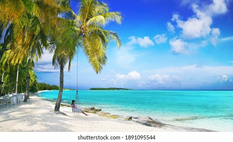 Beautiful natural tropical landscape, beach with white sand and Palm tree, girl is resting on a swing. Turquoise ocean on background blue sky with clouds on sunny summer day, island Maldives.