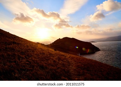 Beautiful natural view of the landscape with the shore with stouns and rocks, lake, and blue sky with sun on sunny autumn day