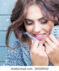 Beautiful natural young brunette smiling woman with eyes closed, wearing knitted scarf, covered with snow flakes. Snowing winter beauty concept