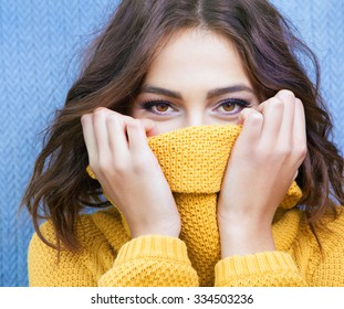 Beautiful natural young shy brunette woman with smiling eyes wearing knitted sweater
