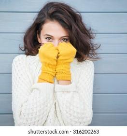 Schöne natürliche junge lächelnde Brunette Frau mit Strickpullover und Handschuhen. Herbst- und Wintermodekonzept.