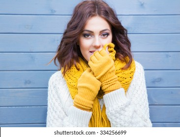 Beautiful natural young smiling brunette woman wearing knitted sweater and gloves. Fall and winter fashion concept.