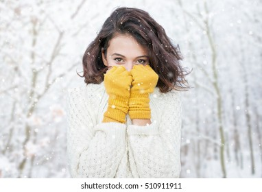 Schöne natürliche junge, lächelnde Brunette Frau mit Strickpulli und Handschuh im Wald. Schneeschwinterkonzept.
