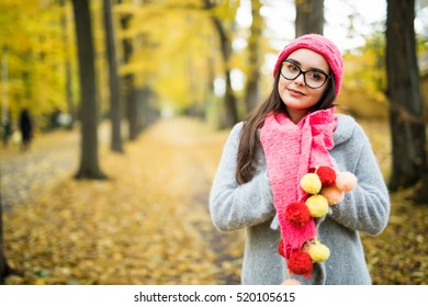 Beautiful natural young smiling brunette woman wearing knitted sweater, gloves, scarf and hat.