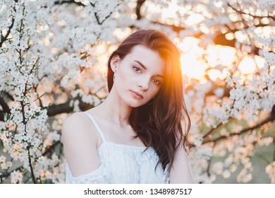 Beautiful natural young woman and spring flower blossoms