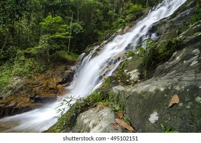 beautiful in nature, amazing cascading tropical waterfall. wet and mossy rock, surrounded by green rain forest