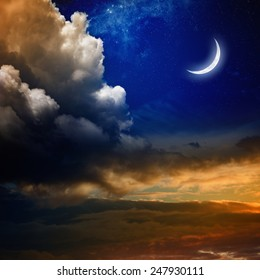 Beautiful nature background - new moon in dark blue sky with stars, glowing sunset clouds. Elements of this image furnished by NASA nasa.gov