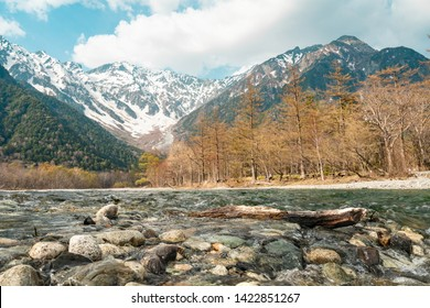 Beautiful Nature Background and Wallpaper of Close up Colorful Rock and Log in Turquiose Crystal Clear Azusa River and Snow Mountain under Cloudy Blue Sky in Kamikochi Nagano Japan