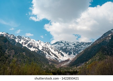 Beautiful Nature Background and Wallpaper of Snow Mountain Peak under Cloudy Blue Sky and Top of Pine Trees Forests Reflect Sunlight in Kamikochi Japan., Place for Nature Lover, Camping Hiking