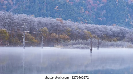 Beautiful Nature Background and Wallpaper of Vibrant Autumn Forest Covered by Snow Reflected in Still Pond with Morning Mist in Kamikochi; Switzerland of Japan in Nagano, Tourist Destination in Autumn