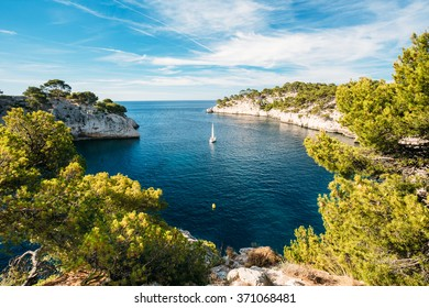 Beautiful nature of Calanques on the azure coast of France. Calanques - a deep bay surrounded by high cliffs. Boat leaves from bay to open sea.