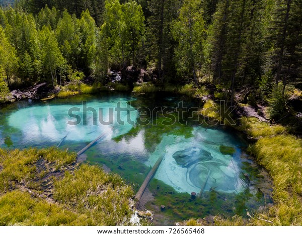 Beautiful nature landscape. Blue geyser lake in forest from aerial view, Altai mountains, RUSSIA, ALTAI REPUBLIC