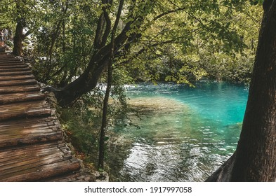 Beautiful nature landscape of blue lakes, waterfalls and green trees in forest, Croatia, Plitvice National Park, wooden bridge