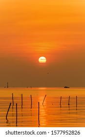 Beautiful nature landscape bright yellow sun reflecting orange light on the water surface of the sea and golden sunlight in sky, Colorful sunset at the tropical coast in Bangpu, Samut Prakan, Thailand
