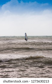 Beautiful nature landscape. Extreme amazing sea. Adrenaline sport freedom. Mans rides on board kite on the wave. Windsurfing people hobby. Inspiring panorama view.
