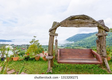 Beautiful nature landscape fog in the valley and swing made of wood on the hill at the high angle viewpoint. Famous tourist attractions at Khao Kho district, Phetchabun province Thailand