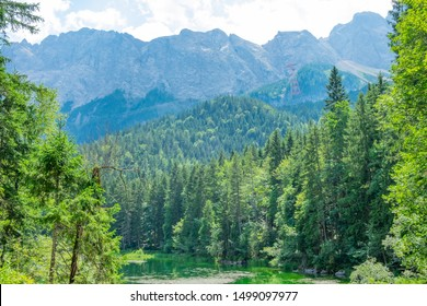 """Beautiful nature landscape: forest, mountains and green lake with tourists in the summer time. The Eibsee Lake and part of Frillensee Lake in Bavaria, """"Zugspitze"""" Alps, Germany"""