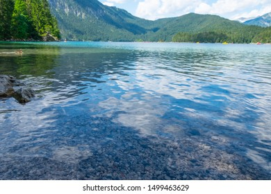 Beautiful nature landscape: forest, mountains and blue green lake with people in the summer time. The Eibsee Lake in Bavaria, Alps, Germany. Close to Garmisch- partenkirchen region
