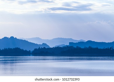 beautiful nature landscape of lake with mountain background with fog and cloud sky in the morning