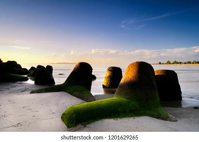 Beautiful in nature, morning scenery along the seashore with groyne structure. Sandy beach and blue sky background