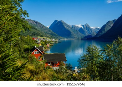 Beautiful Nature Norway natural landscape. Amazing fishing house on fjord. Beautiful nature with blue sky, reflection in water, rocky beach and fishing house. Norway.
