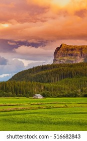 Beautiful nature of norwegian landscape or rural farm with mountains, forest, sunset sky in Norway, Scandinavia, Europe