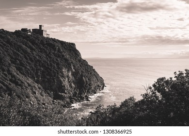 Beautiful nature on Livorno rocky coast. On background Sonnino Castle on a cliff overlooking the sea. Black and white. Livorno, Tuscany, Italy