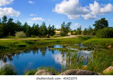 Beautiful nature park on a summer day in city of Ventspils, Latvia. This is a clean and green park with a small lake inside of it. Clouds, sun and silence it's a good atmosphere for relaxation.