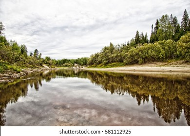 Beautiful nature of the river in the forest, the sky is reflected in water. Russia, Taiga
