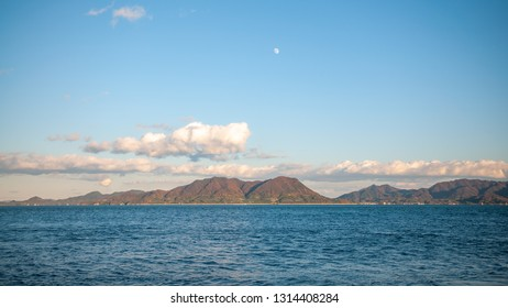 """Beautiful nature scene seen on the island of Okunoshima, also known as the """"Bunny Island"""", which is a small island located in the Inland Sea of Japan, with a waxing gibbous moon in the sky."""