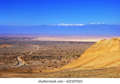 Beautiful nature view - colorful ground with dry bush, twisty country road and yellow rock at the background of bright blue sky and mountain range in Maranjab desert near Kashan, Iran, Middle East