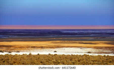 Beautiful nature view, surface of Namak lake with multicolor stripes of dried white salt, yellow sand and blue water at the background of sunset sky in Maranjab desert near Isfahan, Iran, Middle East